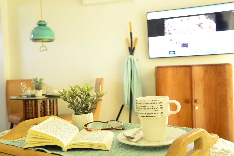 Disfruta de un buen libro (incluimos una pequeña selección de libros para lectura). mientras te tomas una taza de café.