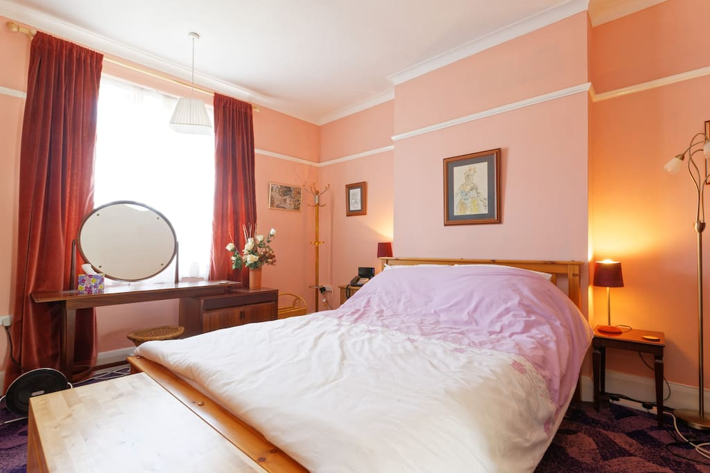 Delightful large bright bedroom available for reservations and overlooks garden. Fully furnished with dressing table, kingsize bed and duvet, 2 wardrobes with hangers, lamp, bedside table and chest of drawers. Lots of provisions for you to unpack and put away your clothes and belongings.