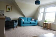 Bright spacious lounge with beautiful views over village and river to the hills beyond.