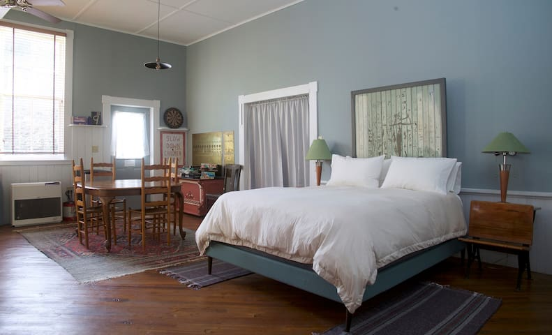 Guest room queen bed and table with 4 chairs. Heavy grey curtain was added to the barn door frame in summer 2019 for sound and light blocking purposes.
