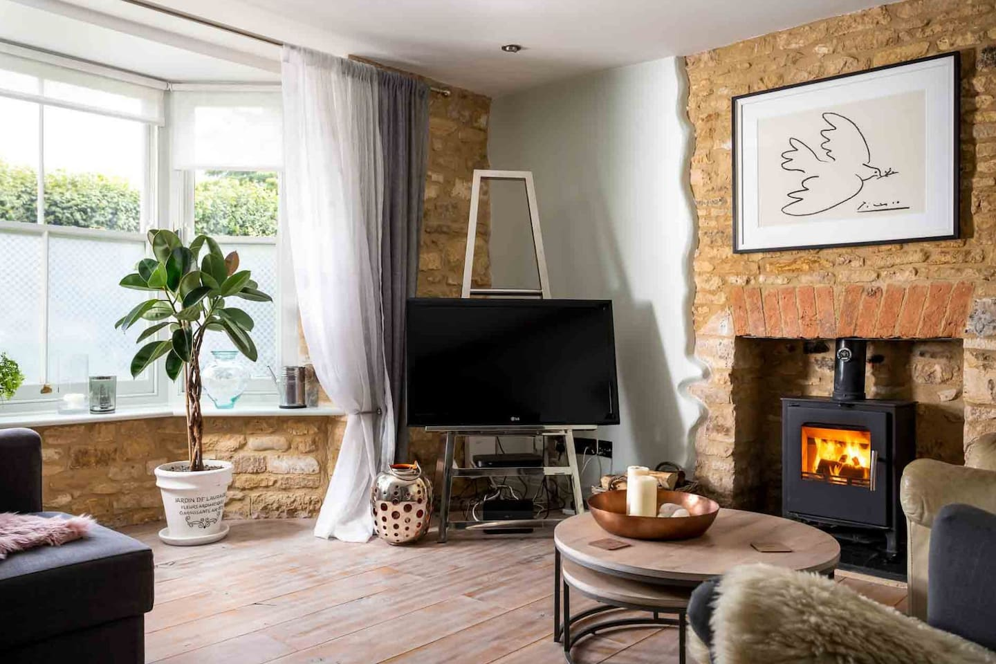 There is a lovely Cotswold stone fireplace with a cosy wood burning stove...