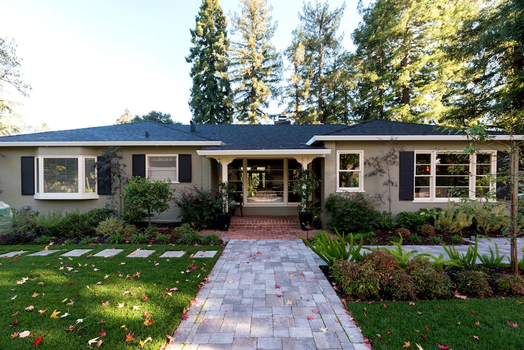 Quiet property with professional landscaping, outdoor lighting,and surrounded by large trees. Master bedroom bay window is on the left.