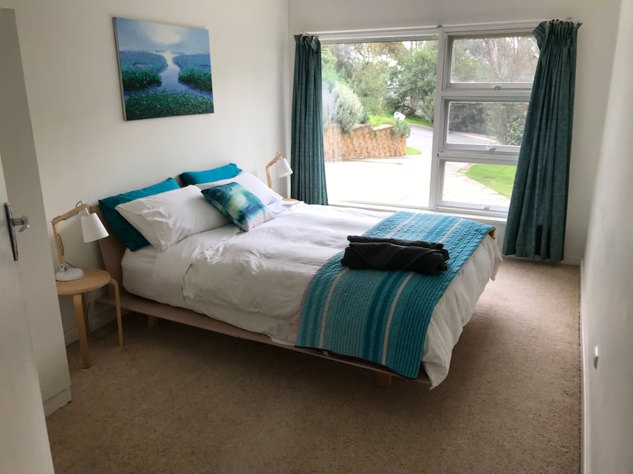 Spacious master bedroom with double robe (out of frame), comfy bed and quality pure cotton linen. There is also plenty of room for the portacot.
