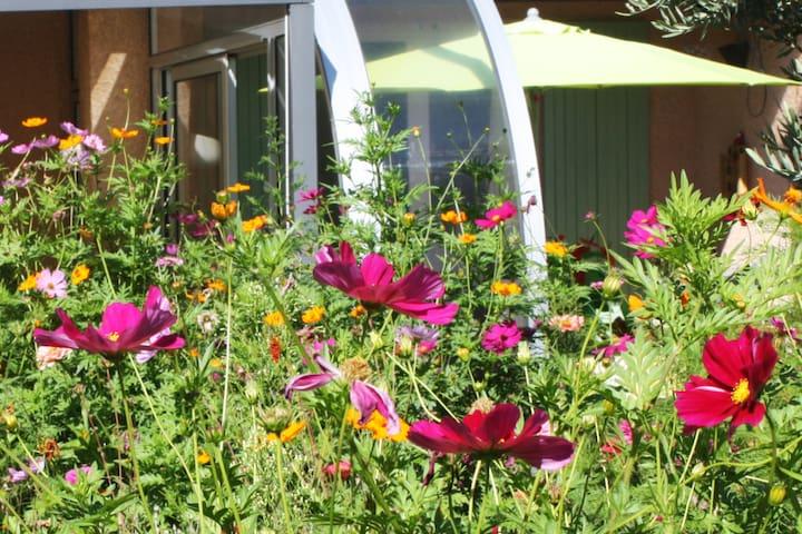 Les Loris. Chambre privée dans jardin fleuri.