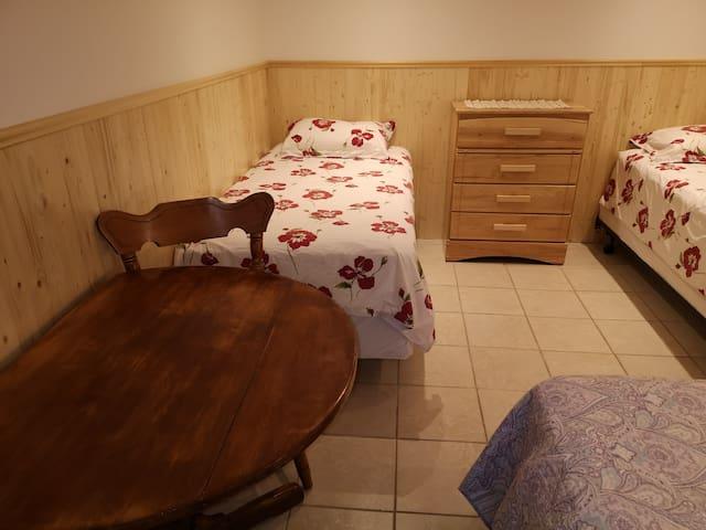 Les trois lits simples, table de travail et petit bureau de la petite chambre