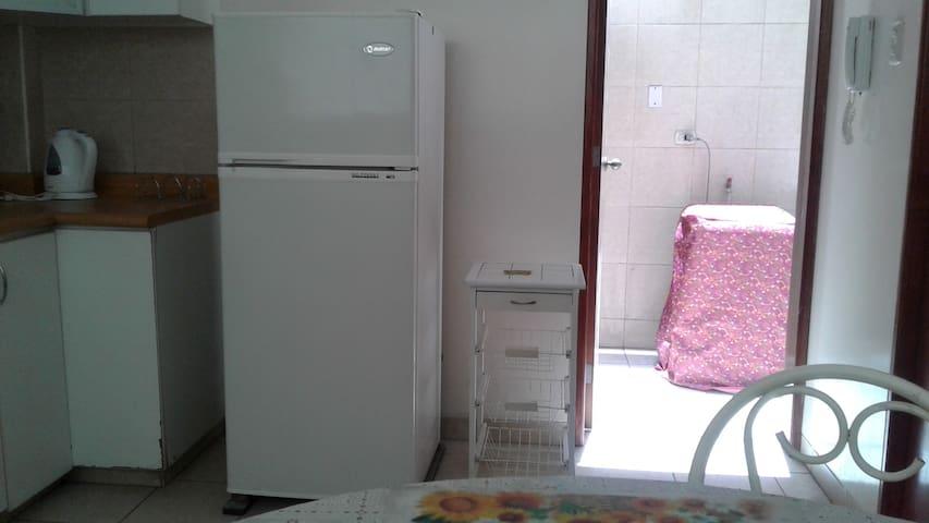 Cocina de otro angulo que muestra la refrigeradora y la lavadora y un espacio de lavandería