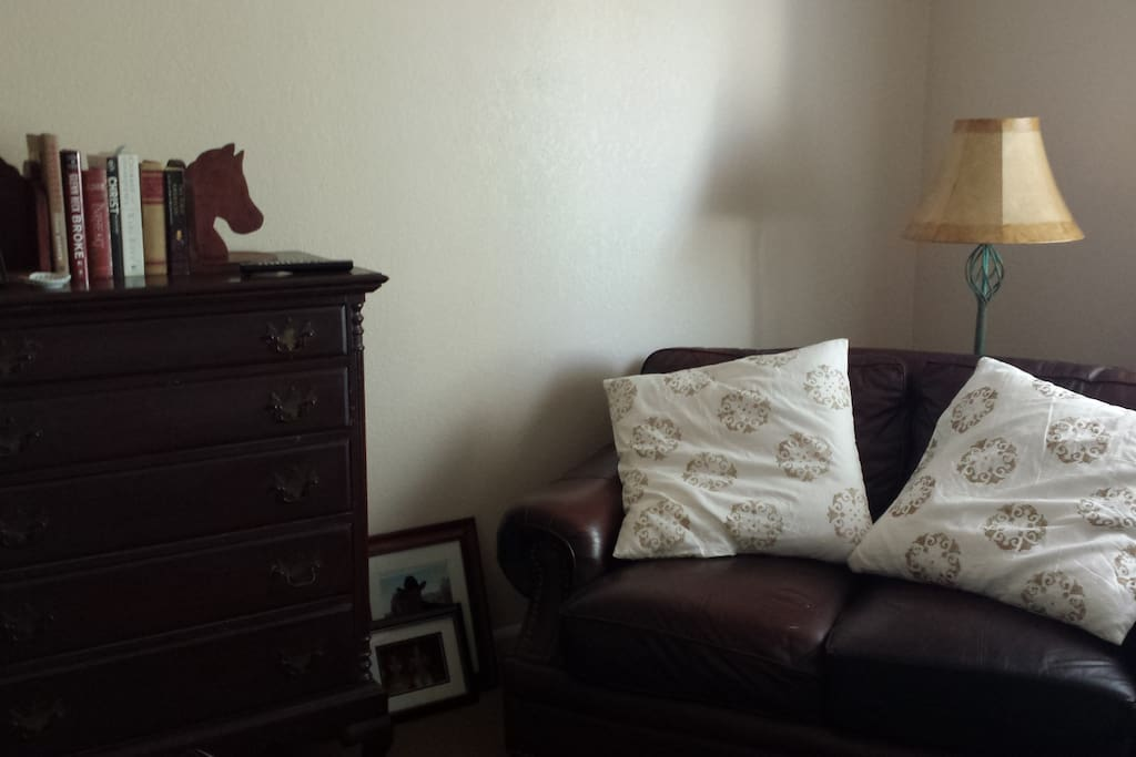 Adjacent TV/living/reading room with leather chair and love seat.