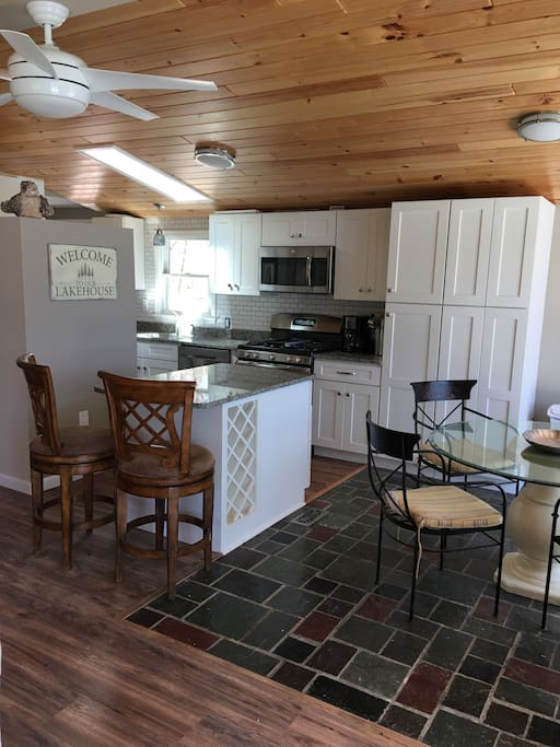 View of the kitchen, island, and glass top table