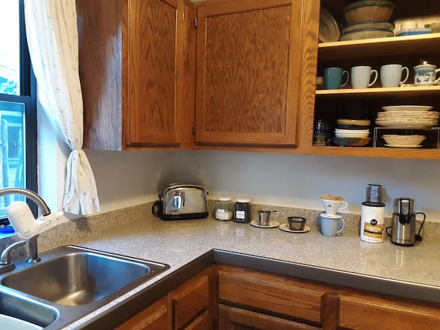 Granite counters and wooden cabinets.  PUR water filter installed on kitchen faucet. Coffee maker and several drip methods of making fresh ground coffee, with or without paper coffee filters.   Microwave in adjacent laundry room.   Toaster.