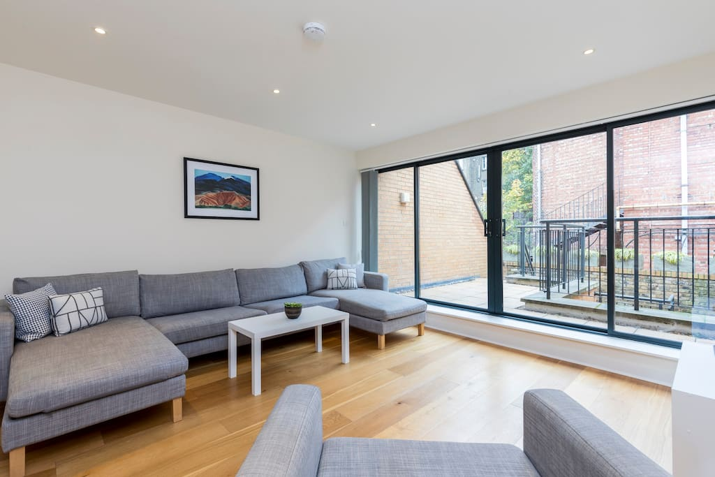 The stylish living area has huge glass doors to let in lots of natural light and access to a terrace.