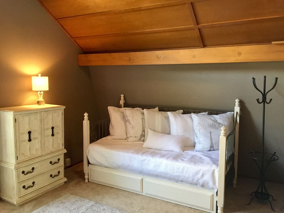 Twin bed with trundle next to bathroom entrance