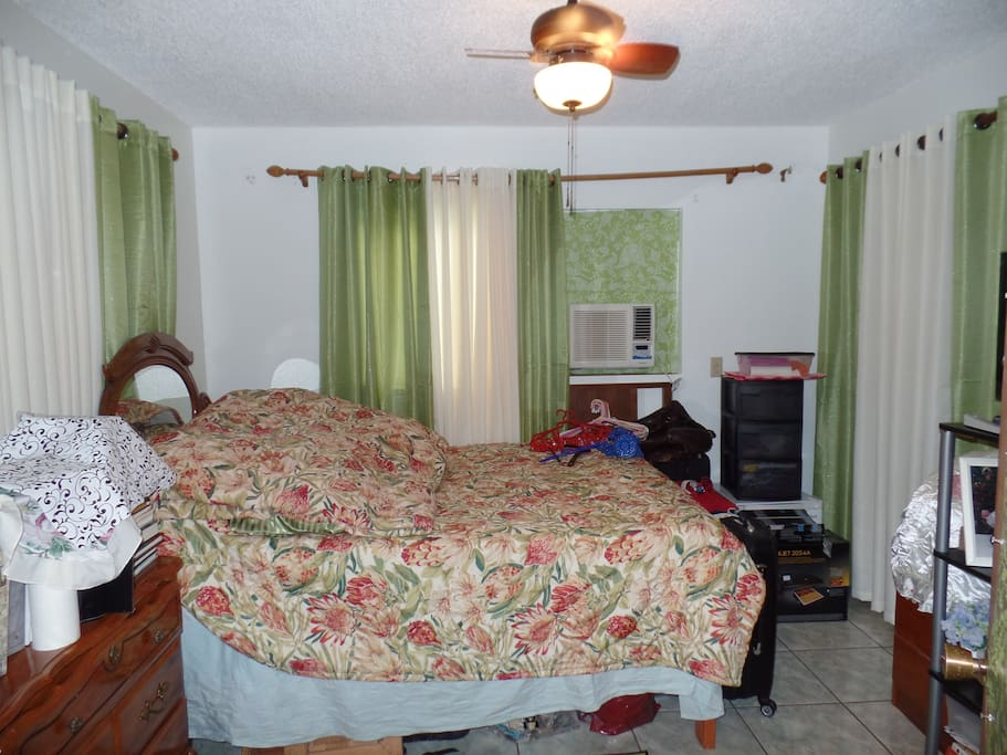 first room queen bed, with ac, with small ice box, with closet covered with curtain, with ceilinng fan