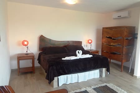 King size bed and closet furnished with modern Mexican rustic style