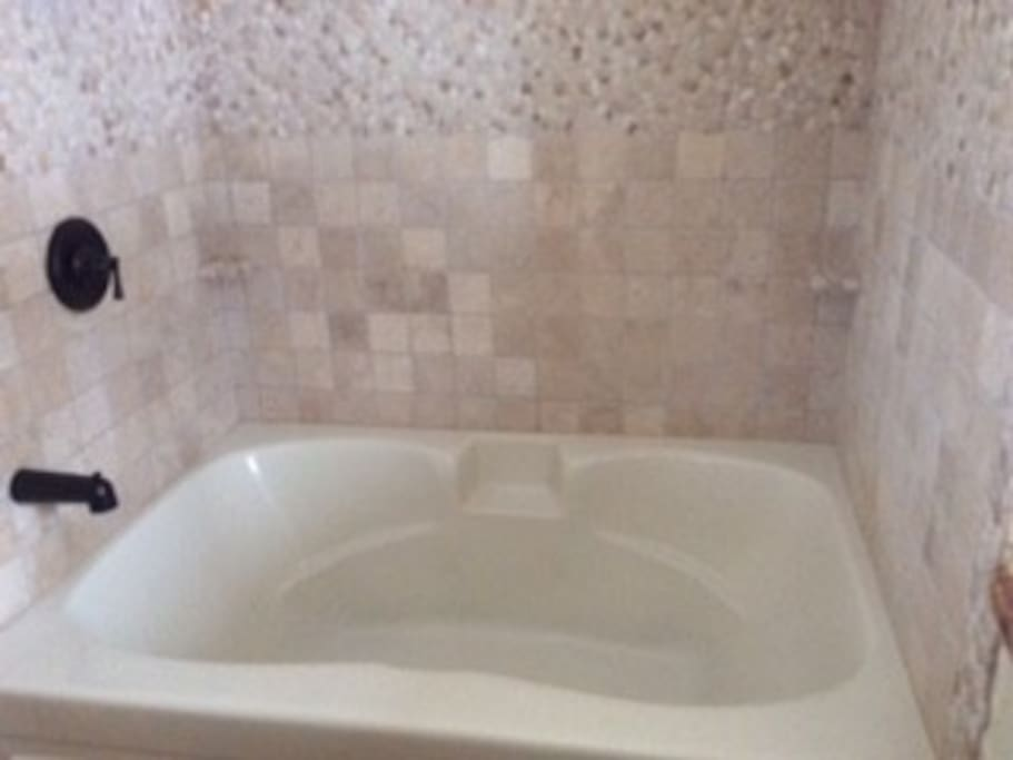 Two-person soaking tub, custom tile, and vessel sink in bathroom.