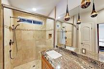 Travertine tile and glossy granite adorns the en-suite master bathroom