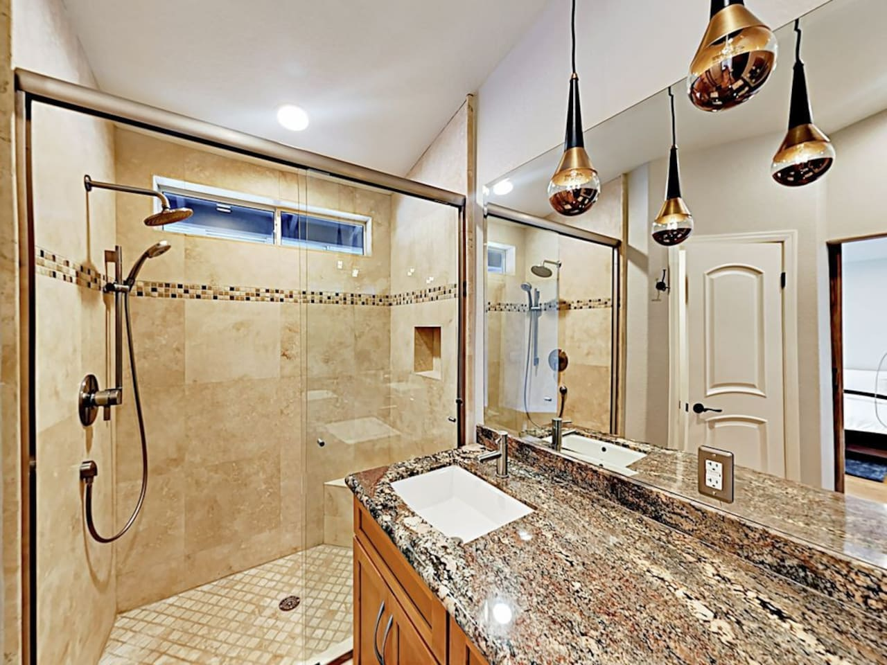 Travertine tile and glossy granite adorns the en-suite master bathroom