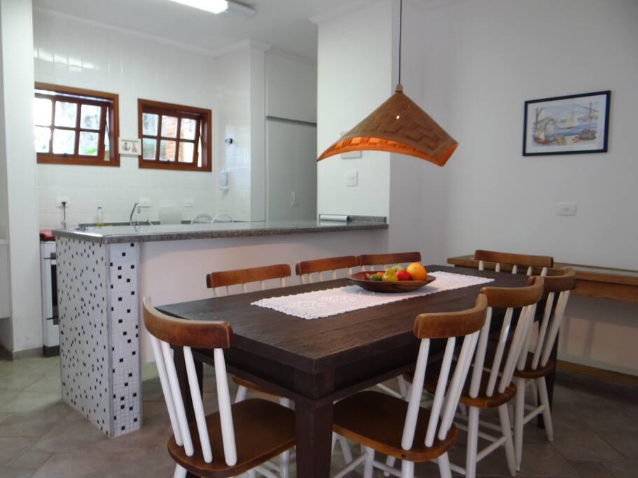 Mesa central integrada com a cozinha.