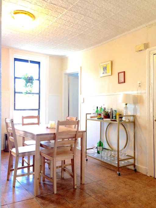 The kitchen has a well-stocked bar cart with cocktail glasses, an eat-in kitchen with room to host four (though we've pulled chairs from other rooms and hosted eight for dinner). The open door opens onto the bathroom.