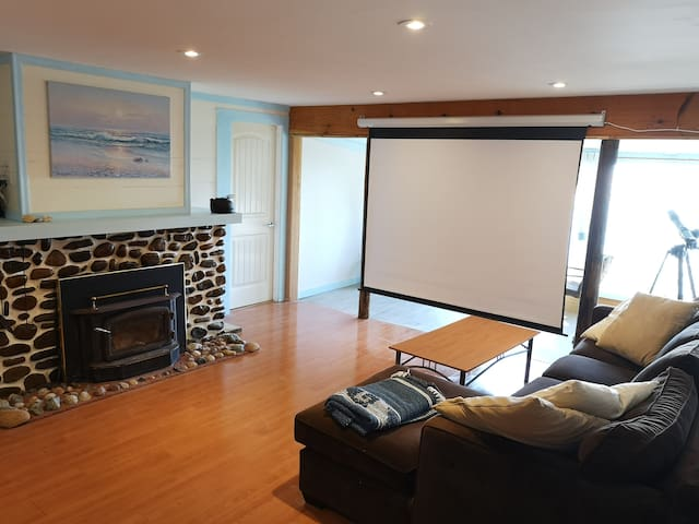 Living room w projection screen down. The projector is an LCD type so not bright for daytime use. There is a flat screen TV on rolling stand you can position where you like.  Screen down also adds privacy to persons on sun porch.