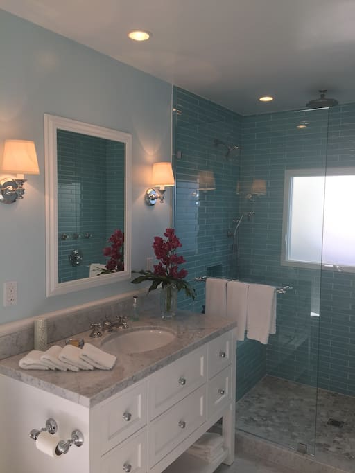 Private bath for guest room. Huge stall shower with three shower heads. Recently remodeled bath has fluffy white towels.