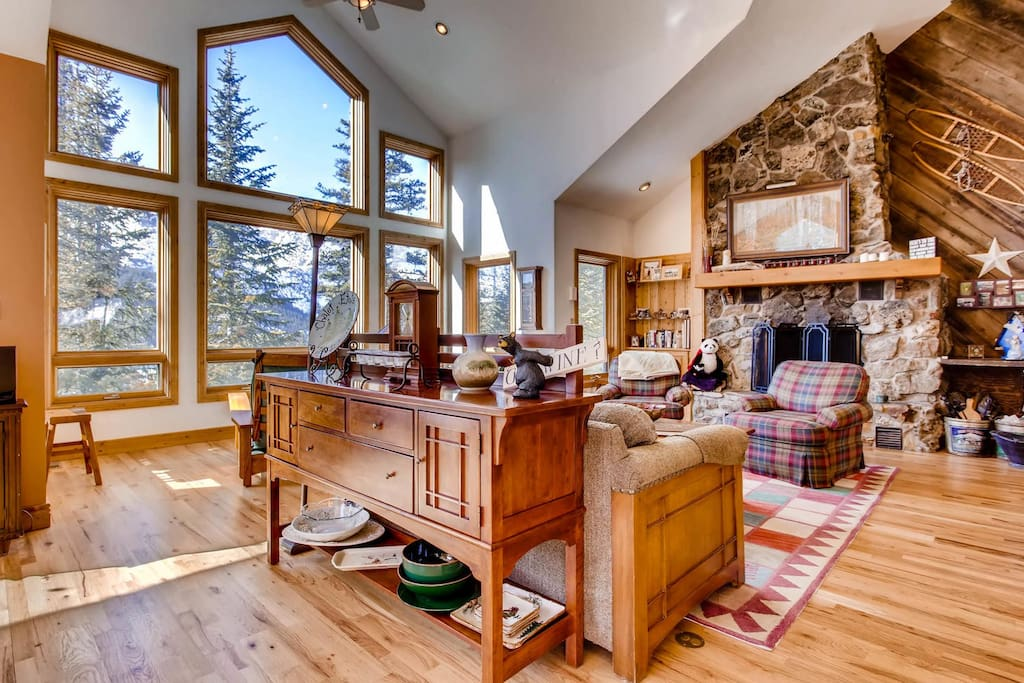 The great room has a fireplace and floor-to-ceiling windows with views of the snow capped peaks of the Continental Divide.