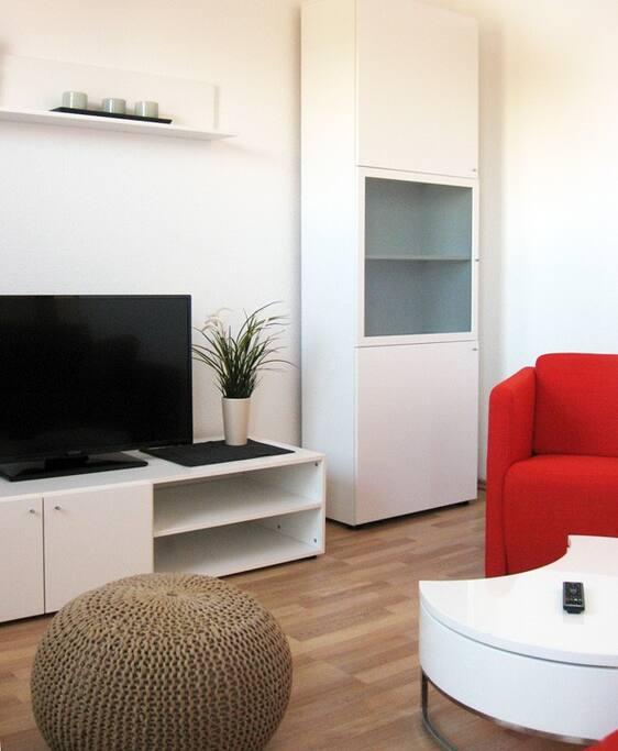 Flat TV und gemütliches Sofa im Wohnzimmer