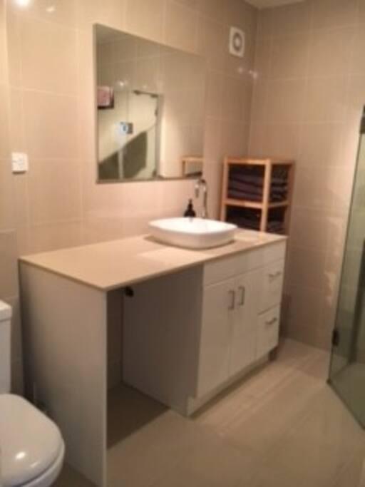Modern fully tiled bathroom with washing machine