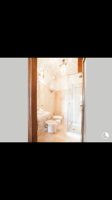 Lovely bathroom with Carrera marble floor & detailing with vintage Lighting