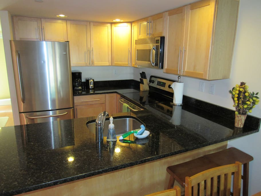 Kitchen with coffee pot, toaster, and stainless steel appliances.