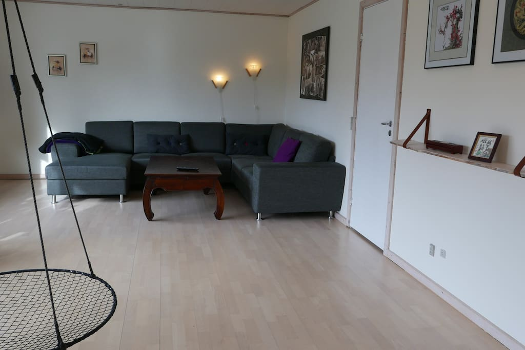 """Living room with 65"""" flatscreen TV and a huge and comfy couch for the whole family"""