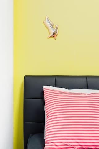 The mustard accent wall is further enhanced by 3D birds by Czech designer Daniel Piršč.