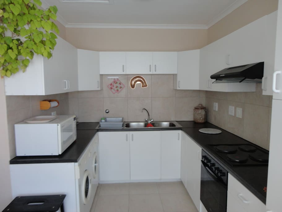 Fully equipped kitchen including stove, oven, washing machine, tumble dryer, microwave.