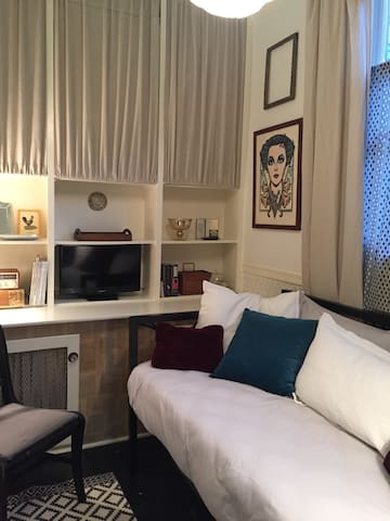 twin bed with lots of pillows - cotton sheets, blanket, feather duvet with cotton cover. television with cable. lots of light; reading lamp at bed, ceiling fixture is on dimmer.