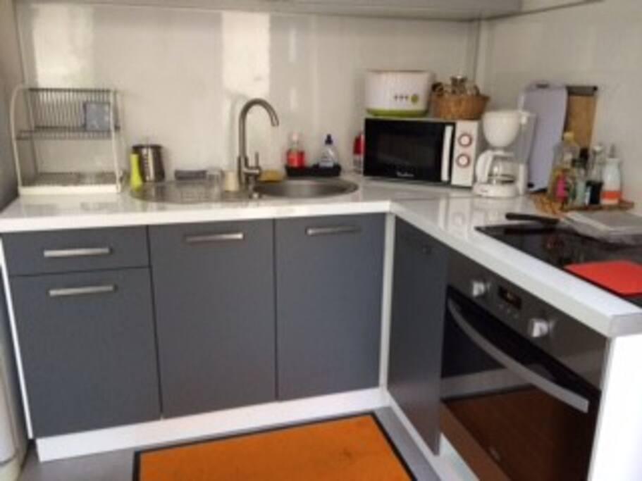 Une cuisine aménagée avec plaque à induction, four et micro-onde, avec la vaisselle et la batterie de cuisine  en conséquence.
