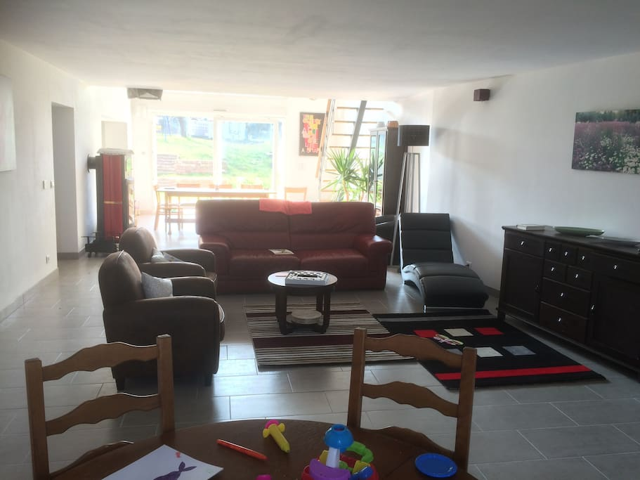 Grand salon avec canapé, fauteuils, table ronde pour jouer ou travailler en plus de la table de repas. Grand arche vitré pour une luminosité maximale.