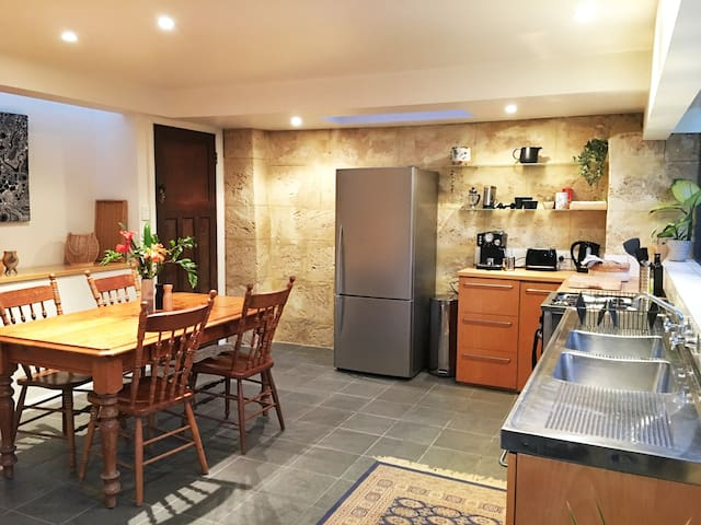 Downstairs kitchen with gas stove and oven, fridge, microwave and coffee machine.