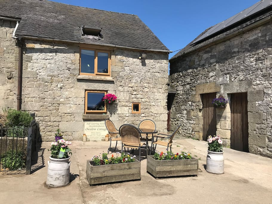 New caption for Summer 2018 - lots of colourful plants and flowers, and new seating at the front of the cottage