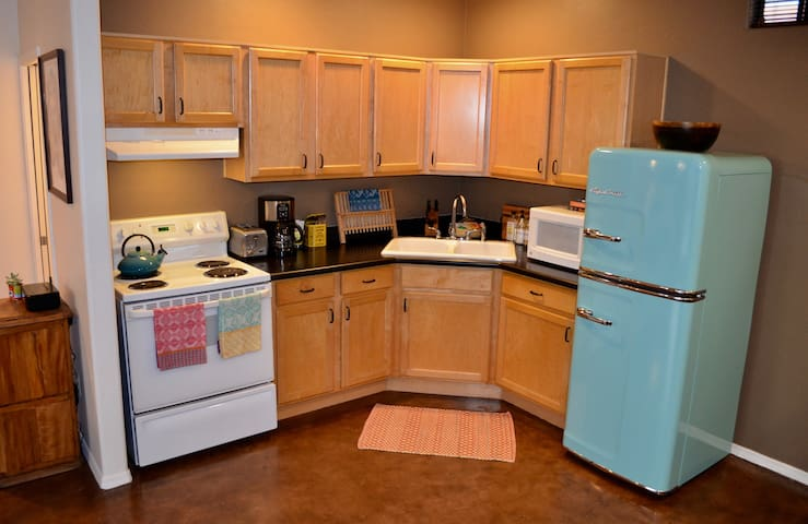 A fully stocked kitchen with oven, fridge, microwave, toaster and coffee maker.