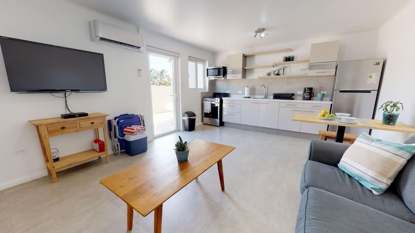 Living room with Smart TV and sofa bed fully equipped Kitchen.