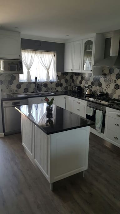 Kitchen with gas hob, dish washer, fridge and microwave