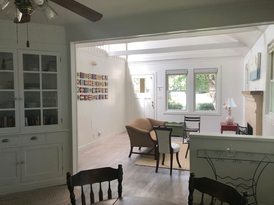 The living room was opened up when the previous owners tore out the attic ceiling and created a loft upstairs with giant skylights. This photo is taken from the entrance to the kitchen showing the small dining space and the living room.