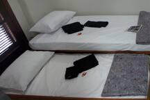 """As 2 camas de solteiro; a inferior, no chamado estilo """"gaveta"""", vistas a partir da porta do banheiro."""