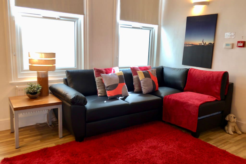 Leather corner sofa which quickly converts into a comfy double bed with double glazed windows out on to the bright lightwell.