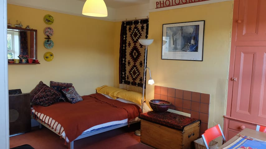 The full size double bed with duvet and knitted throw, cushions and above a mirror and shelf.