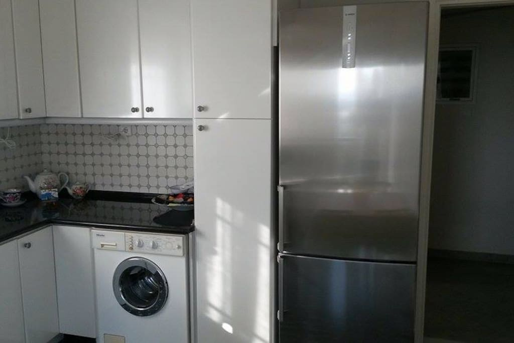 Kitchen area with a fridge, 2x washing machines, one for  clothes and the other for dishes, and an oven.