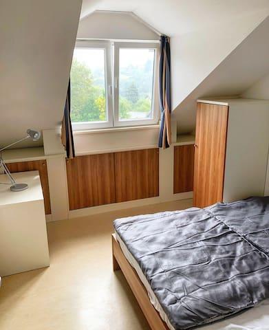 Ruhiges Schlafzimmer mit 2 Betten, Kleiderschrank und Abstelltisch