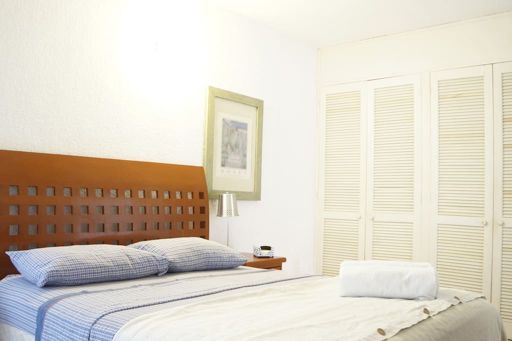 Queen bed with a big closet, air conditioner and fan