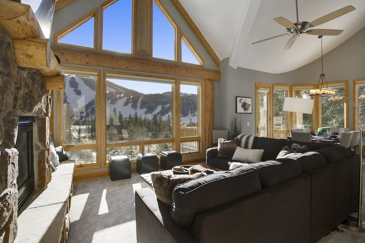 Large main living area with stone fireplace and incredible views of the resort slopes