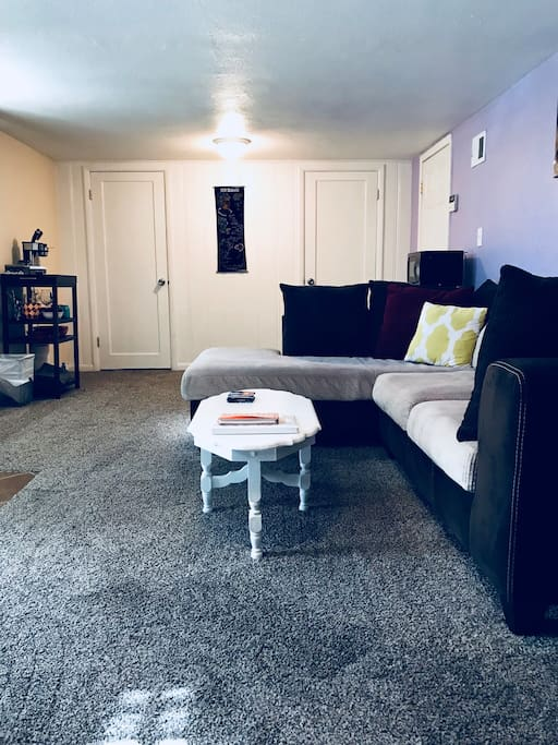 Living area with comfy couch, fridge, microwave, coffee, TV, DVD player and DVDs, Amazon Echo, Chromecast, and plenty of room for air mattress (provided along with extra sheets, pillows, and blankets).