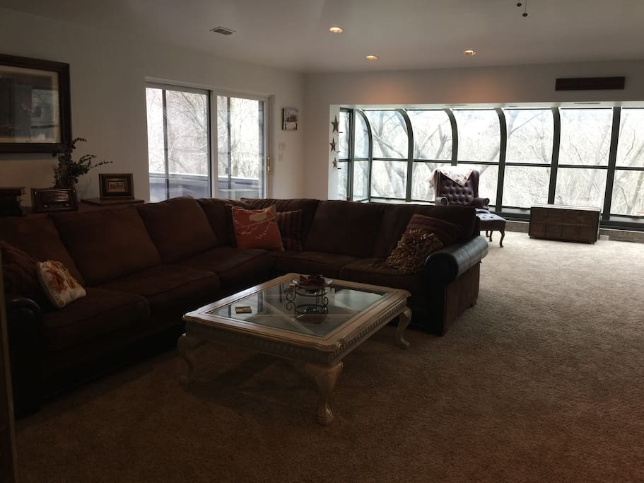 Large sofa in the Great room. Sliding door to patio in the front of the house.
